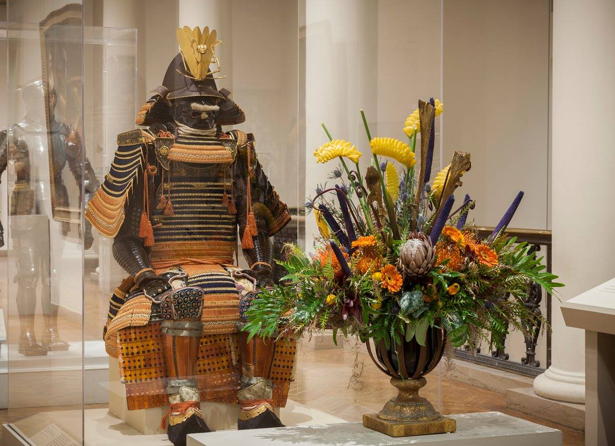 A flower sculpture next to Asian armor at the 2017 Art in Bloom at the Minneapolis Institute of Art