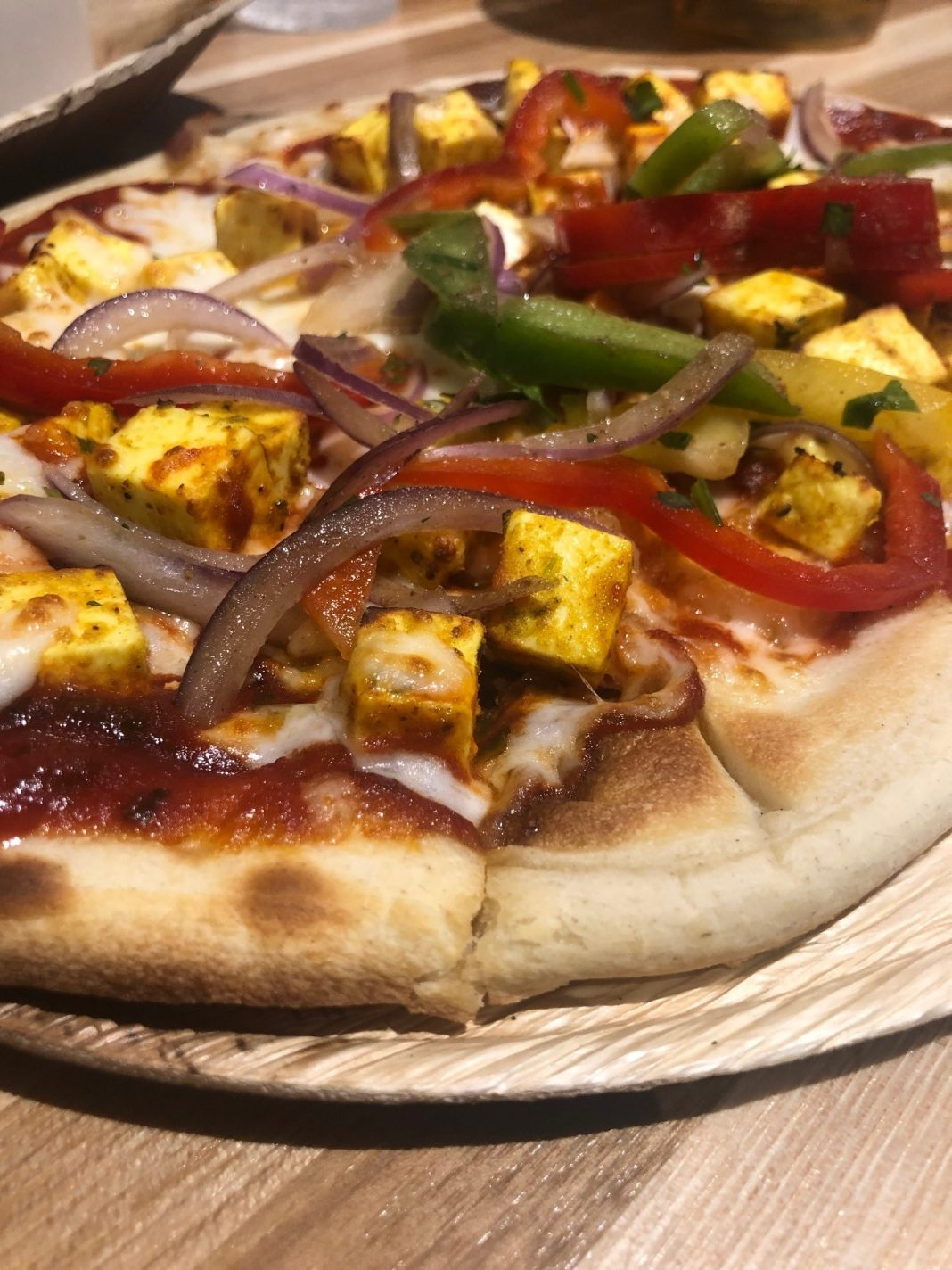 Paneer Pizza ($10) with non-melting cheese marinated in Greek yogurt, lime-kissed peppers, tomato-fenugreek sauce, and fresh mozzarella on plain naan