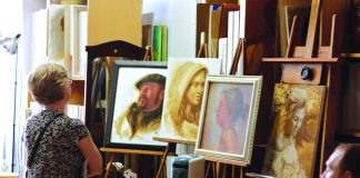 Art-a-Whirl visitor looks at a variety of paintings.