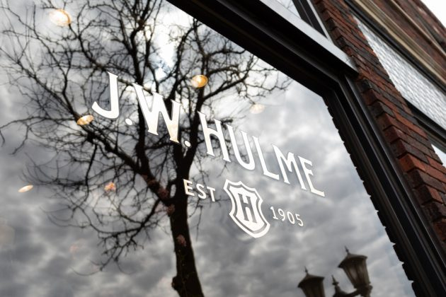 A photo of the J.W. Hulme logo on the storefront window.