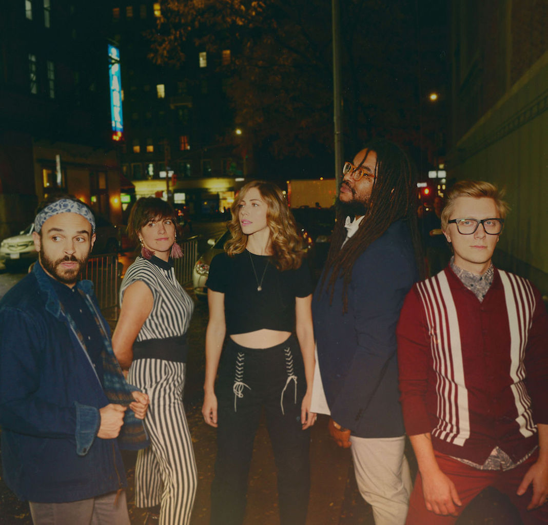 Mike Calabrese, Bridget Kearney, Rachel Price, Akie Bermiss, and Mike Olson — the members of Lake Street Dive — pose outside in a city at night