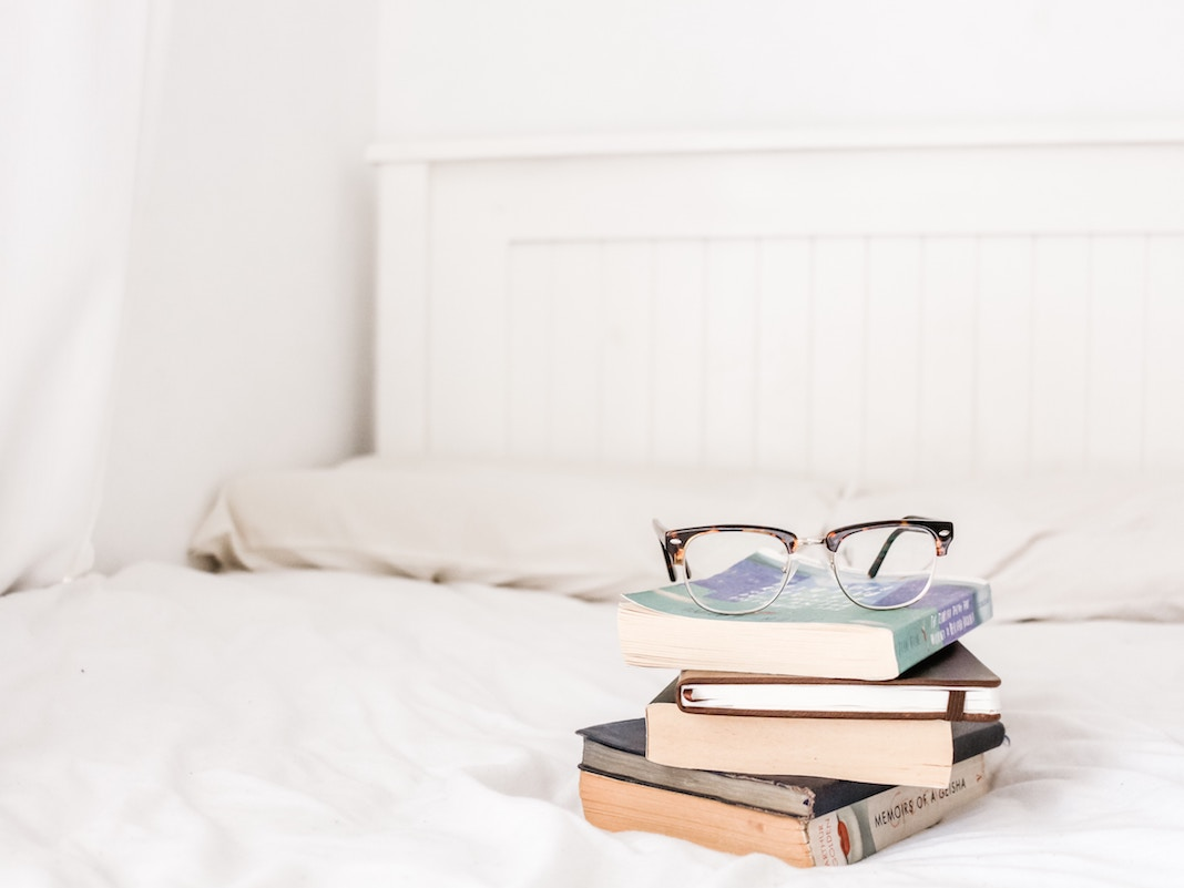 a stack of books on a white bedspread, with a pair of glasses sitting on top of them.