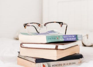 A pile of books on a white bedspread, with a pair of eyeglasses on top of them.