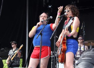 Har Mar Superstar and Sabrina Ellis, the singers of Heart Bones, perform at Rock the Garden. They're both wearing short athletic shorts and bright primary colors.