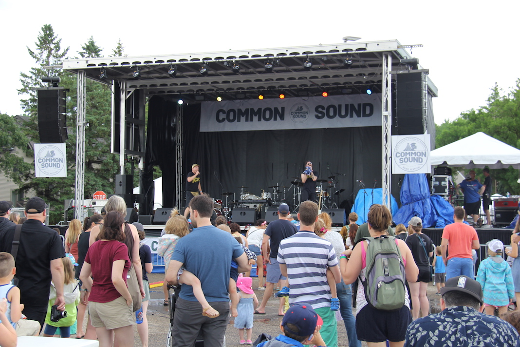 Koo Koo Kanga Roo performs on a stage at Common Sound to a large crowd of young kids and their parents.