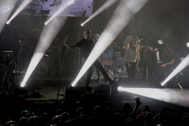 The National performs at Rock the Garden, with lead singer Matt Berninger redirecting the white stage lights with his foot to point one down into the crowd.