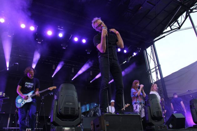 The National performs at Rock the Garden, with lead singer Matt Berninger standing on a speaker. The rest of the band is behind Berninger, and the stage is flooded with purple lights.