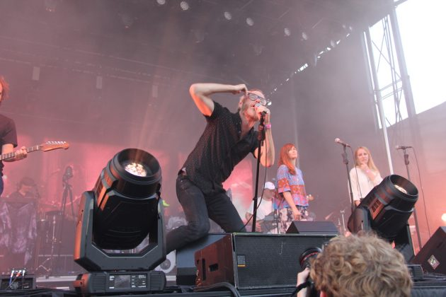 The National performs at Rock the Garden, with lead singer Matt Berninger crouching down. The stage is lit with red lights.