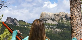 A girl sitting in a hammock looking out at Mount Rushmore