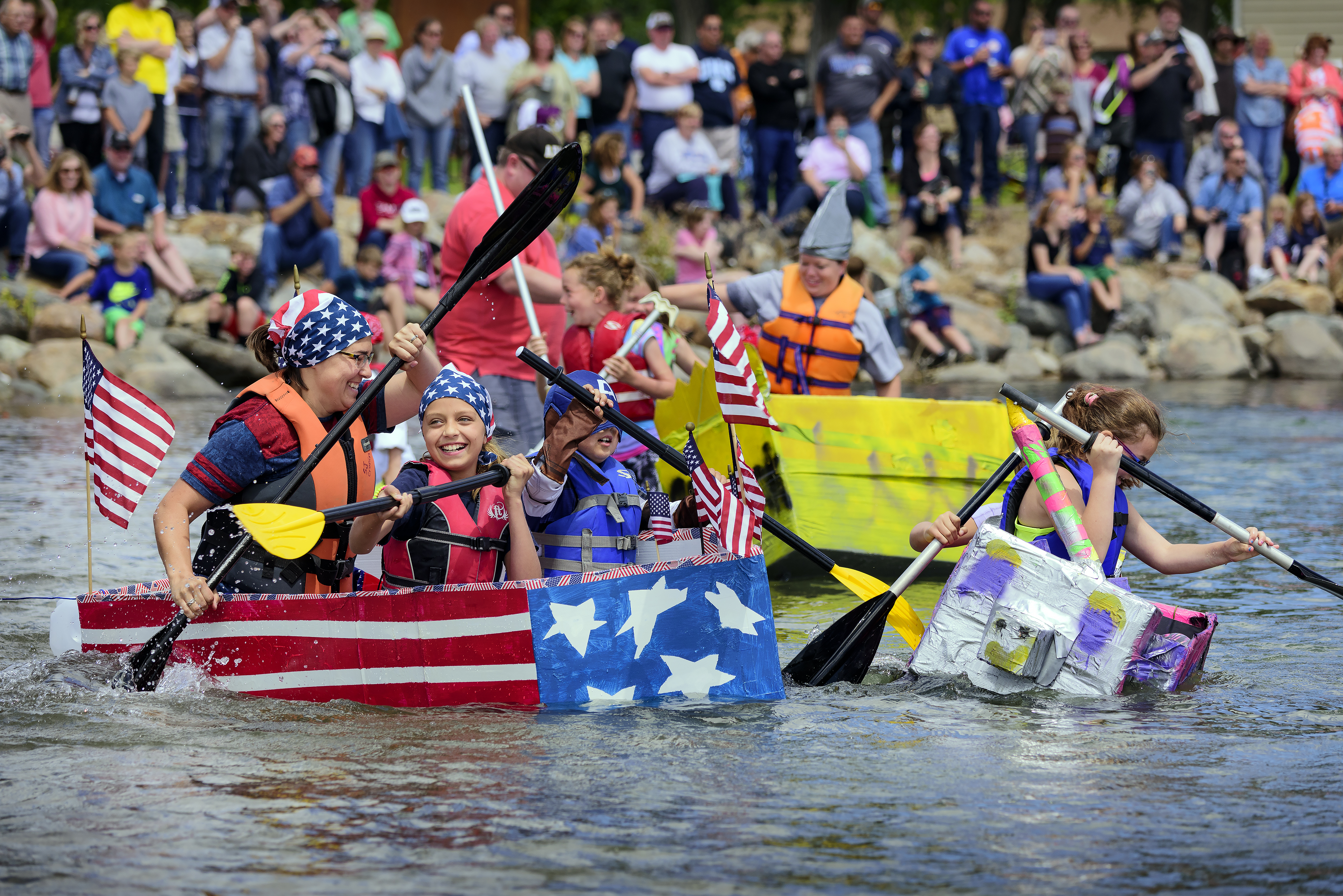People rowing an American flag themed cardboard boat at Oahe Days in South Dakota