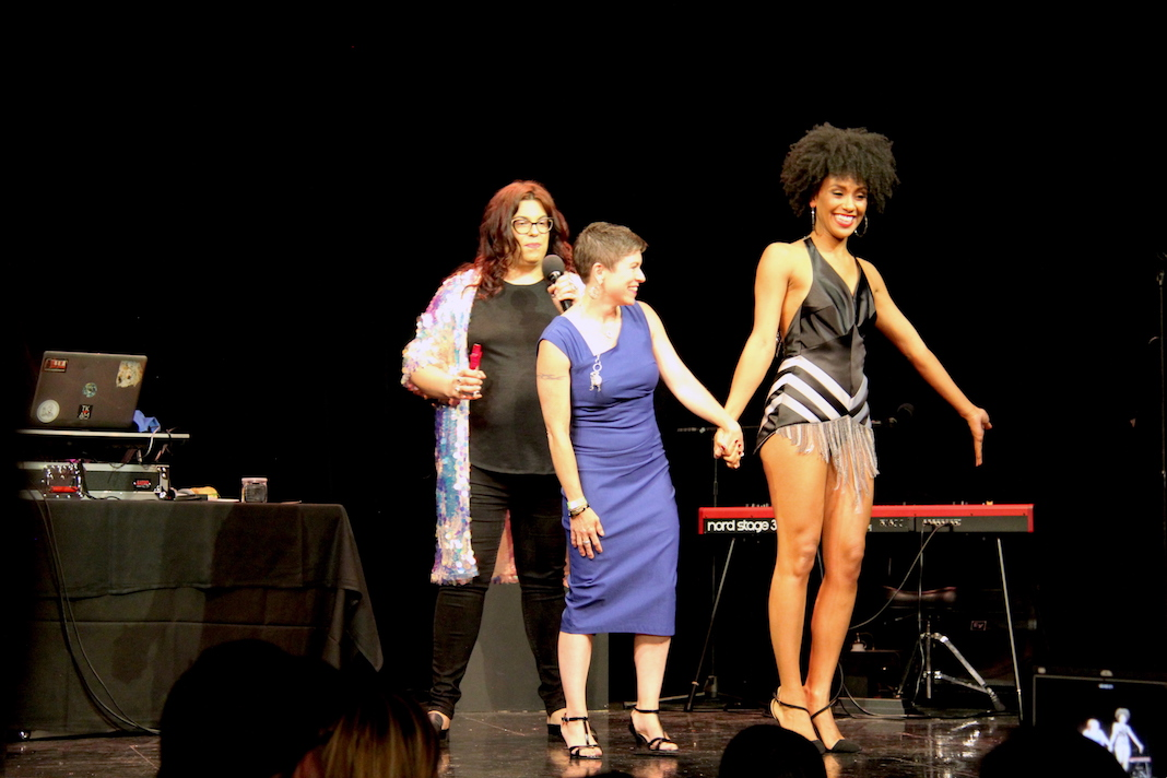 Designer Gay Hacker and model ___, wearing a short black dress inspired by Tina Turner with white chevron and silver fringe on the bottom, return to the stage to accept the Audience Choice award at DesignICON 2