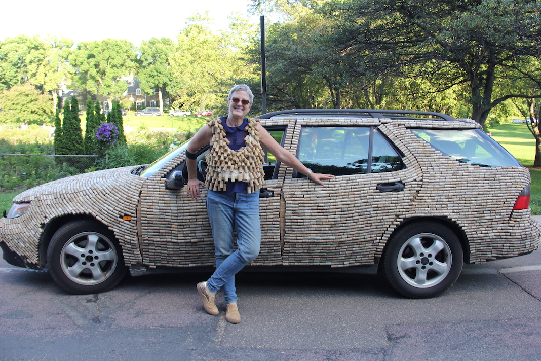 Jen Elftmann, wearing a vest covered in wine corks, leans against her cork car