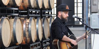 Ross Golan performs The Wrong Man album at Tattersall Distillery, a wall of barrels behind him.