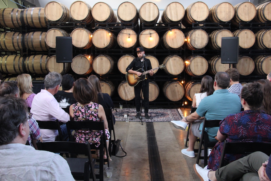 Ross Golan performs The Wrong Man album at Tattersall Distillery, a wall of barrels behind him and a few rows of audience members in front of him.
