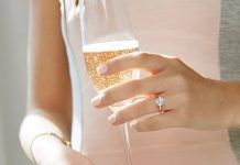 Woman with diamond engagment ring holding champagne