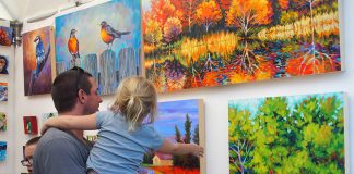 Father and daughter shopping paintings at Spirit of Saint Croix Art Festival