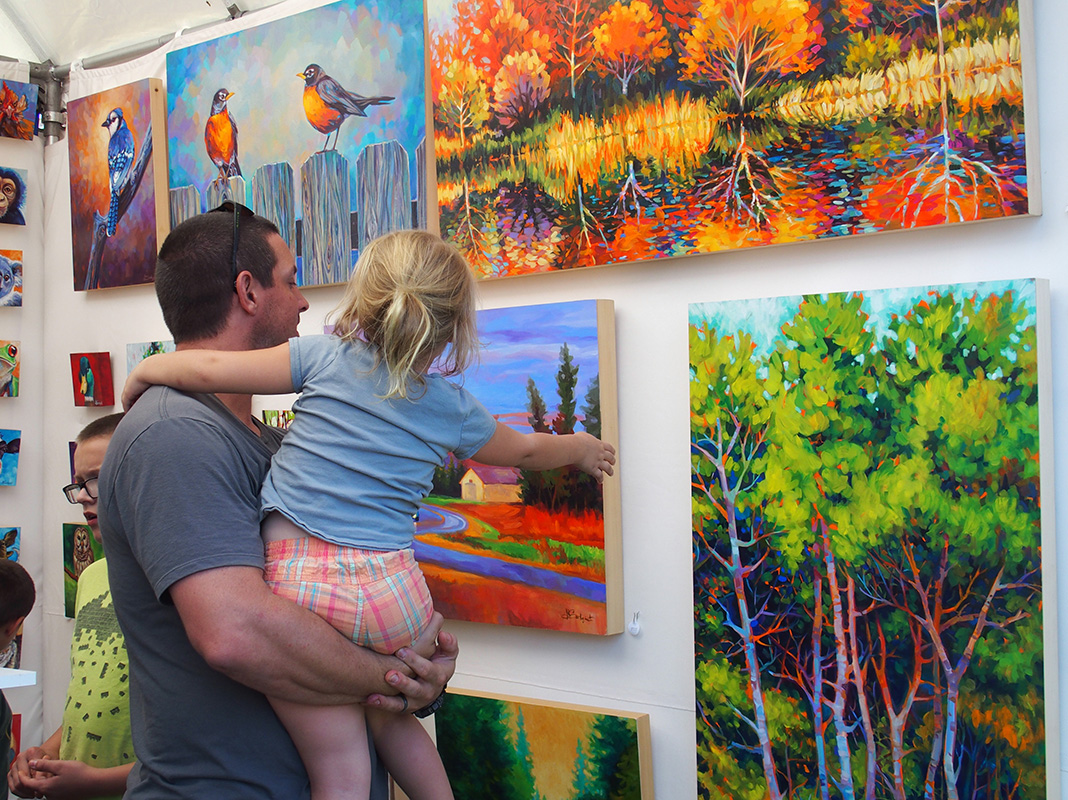 Father and daughter shopping paintings at Spirit of St. Croix Art Festival