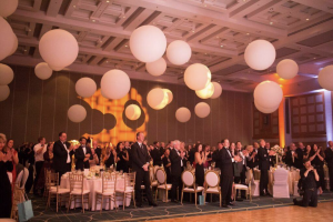 People giving a standing ovation around their dinner tables in an event venue.