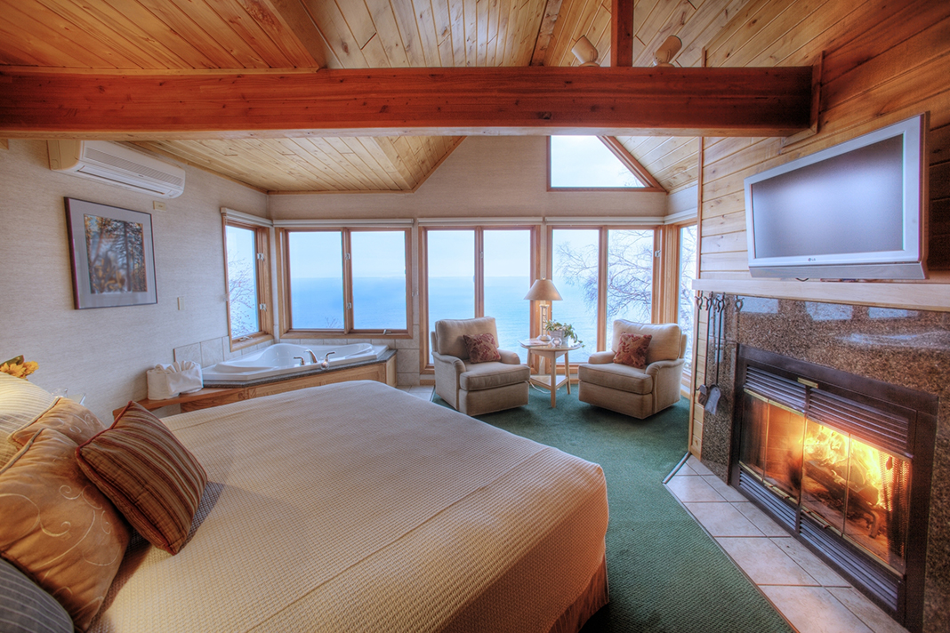 A lakeside resort room with green carpet, a queen-sized bed, jacuzzi tub, and fireplace.