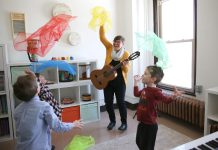 A therapist with Twin Cities Music Therapy Services teaches a class of children.