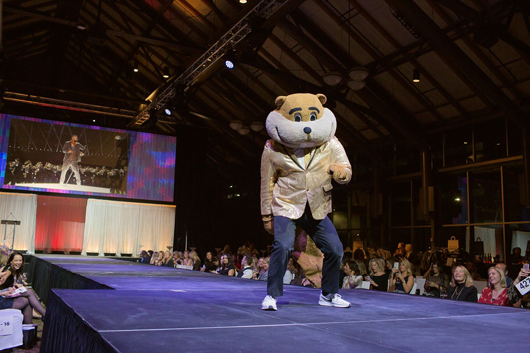 University of Minnesota mascot Goldy, a gopher, walks the FashionFest runway in 2018.