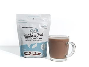 A bag of Mike & Jen's Hot Cocoa and a clear glass mug of hot cocoa next to it