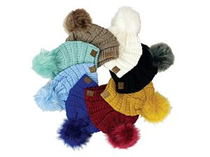 A group of Pom Pom Beanies in different colors from General Store of Minnetonka. Colors include cream, black, mustard, red, blue, baby blue, mint green, and light brown.
