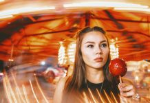 Women with pomegranate candy by whirling carnival ride with lights