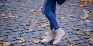 Fall fashion with woman in ankle boots standing on the street with fall leaves around her.