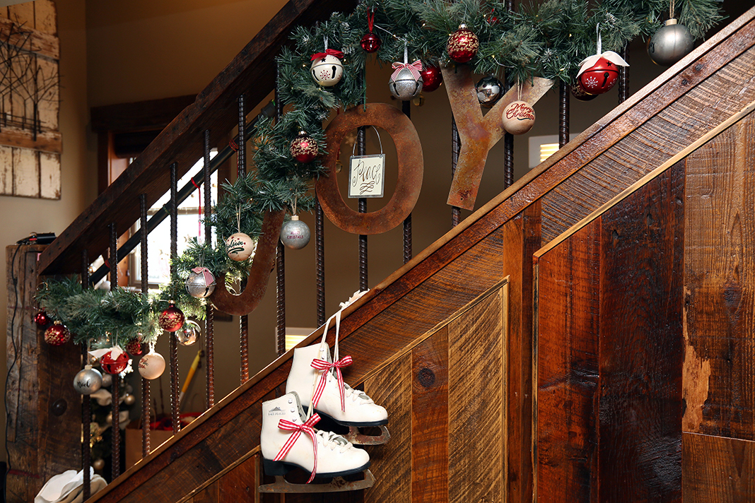 A wooden stairwell with garland, ornaments, and a pair of ice skates as holiday decorations