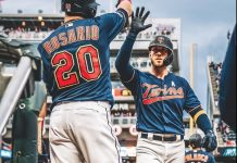 Catcher Mitch Garver high-fives outfielder Eddie Rosario