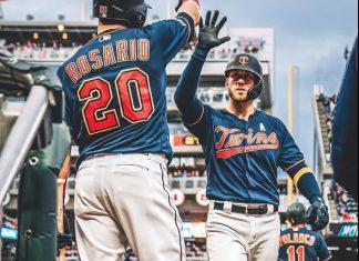 Catcher Mitch Garver high-fives outfielder Eddie Rosario