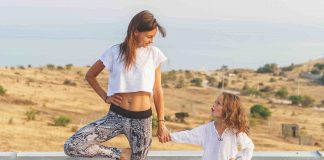 mom and kid stand in a yoga pose on a mat