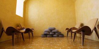 A meditation room with walls made of beeswax, yellow tile flooring, and mid-century modern chairs