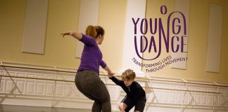 An instructor dancing with young male student