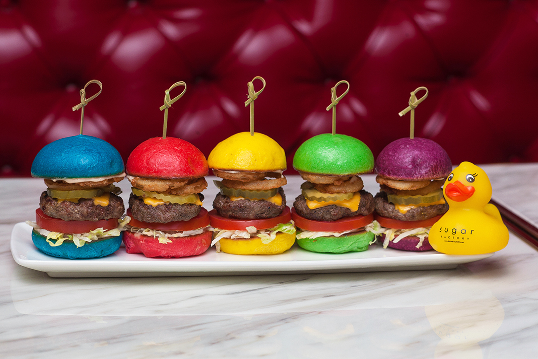 Burger sliders with vibrant colored buns, served with a branded rubber ducky.
