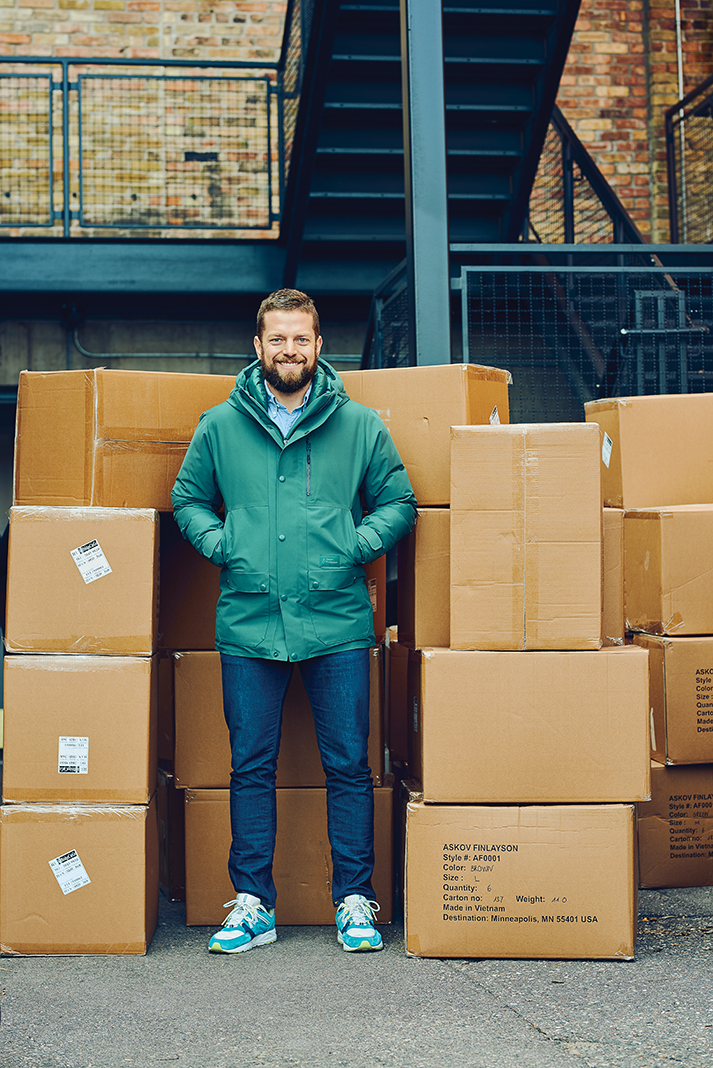 Eric Dayton stands amid a newly arrived shipment of parkas
