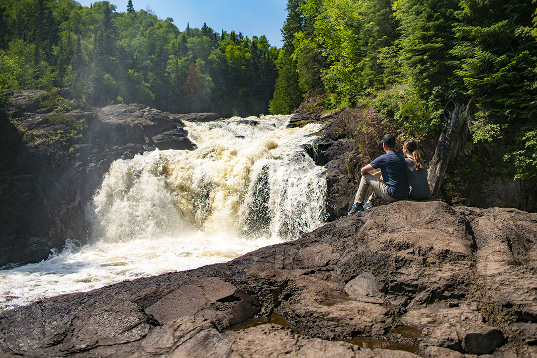 A young couple admiring a waterfall in Cook County, Minnesota.
