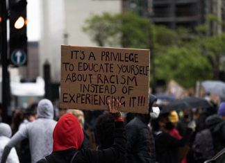"""Protester holds up sign saying """"It's a privilege to educate yourself about racism instead of experiencing it!!!"""""""