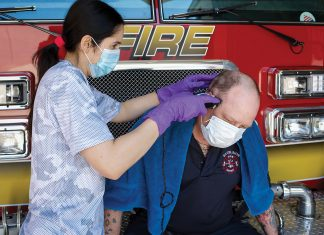 Because salons and barbershops have been off limits, Excelsior Firefighter Thom Brown received his first trim in 8 weeks from administrative assistant Ana Faturri.